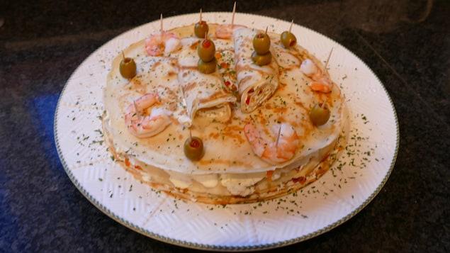 Dans une assiette, des crêpes superposées garnies de crevettes et olives.