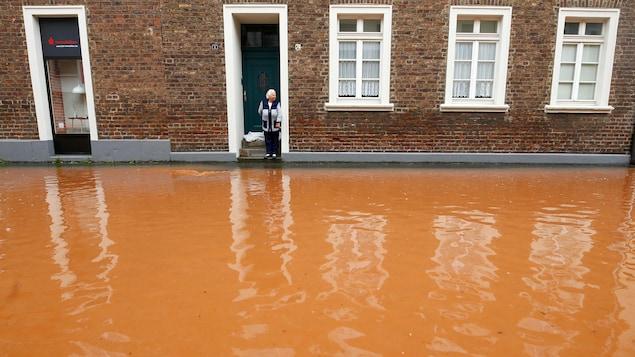 Une femme sur le pas de la porte d'une résidence, devant une rue inondée par une eau brune.
