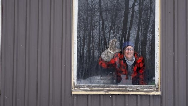 Izabel Zimmer salue la photographe à travers la fenêtre de son érablière.