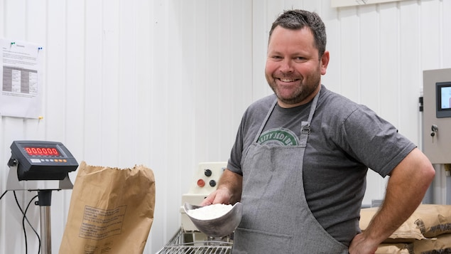 Le boulanger Jean-François Dinelle pose avec une pelle de farine.