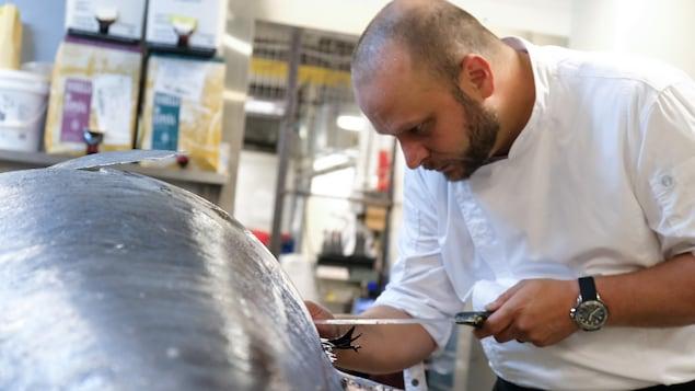 Le chef Patrick Dubé découpe un énorme thon rouge.