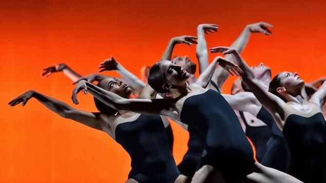 Des danseuses élèvent leurs bras dans les airs et se penchent vers leur droite en regardant le ciel.