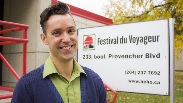 Darrel Nadeau devant un panneau du Festival du Voyageur