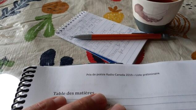 Photo en gros plan d'une main posée sur un document relié par un boudin noir, portant le titre « Prix de poésie Radio-Canada 2019, Liste préliminaire » posé sur une toile cirée fleurie. En arrière plan, un carnet de notes, un pousse-mine et une tasse de thé.