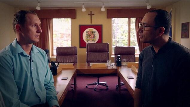 On voit les deux hommes en entrevue, de profil. En arrière-plan, une table et des chaises dans une salle de réunion.