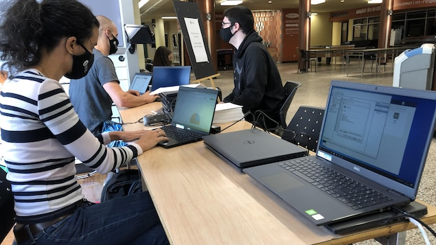 Des gens devant des ordinateurs portables
