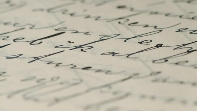 Des lignes d'écriture noires sur une feuille de papier blanc