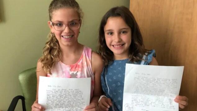 Deux élèves posent fièrement avec leur lettre dans les mains.