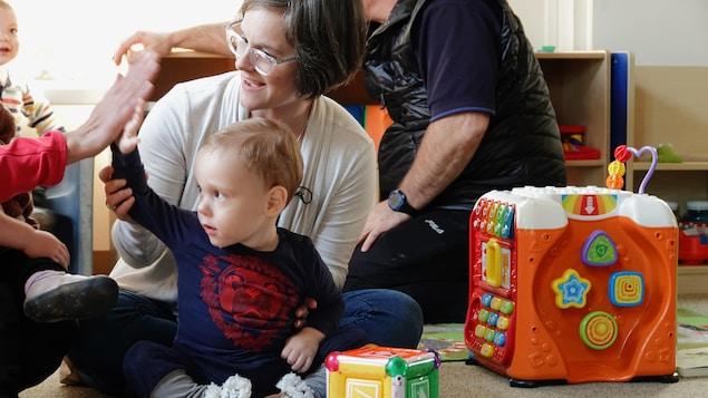 Elliot, qui est tenu par sa maman, tape dans la main de son éducatrice.