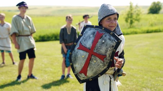 Un enfant habillé en chevalier dans un champ.
