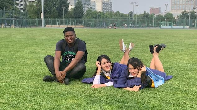 Un jeune homme africain assis sur un terrain gazonné avec deux amies chinoises.