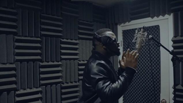 Un artiste chante devant un microphone, dans un studio insonorisé.