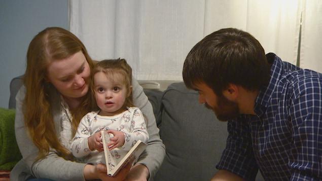 La famille Malenczak-Dunn lit un livre sur le sofa.