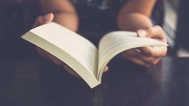 Gros plain sur les mains de la lectrice et sur le livre.