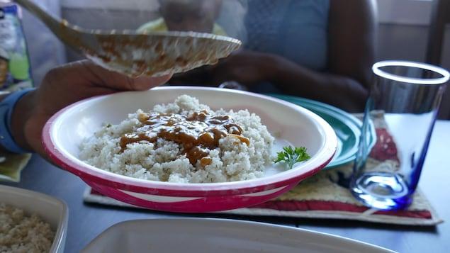Une main tient l'assiette de fonio et avec une cuillère verse la sauce au beurre d'arachide dessus.