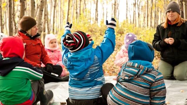 Deux adultes sont assises avec des enfants dans une forêt en automne.