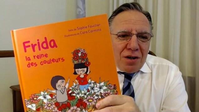 François Legault tient un livre pour enfants près de son visage.