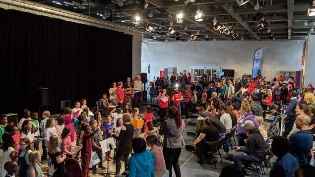 Une salle avec une foule qui regarde une scène.