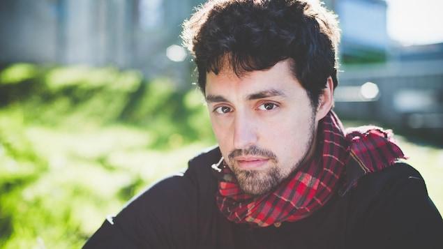 Portrait en couleur de Frédérick Lavoie. Il porte un chandail noir et un foulard à carreaux rouges.