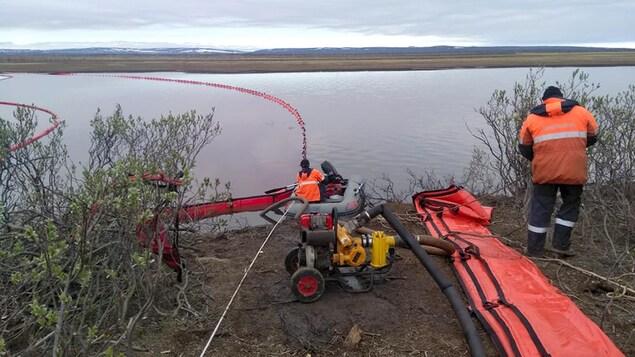 Des travailleurs s'affairent près de bouées destinées à contrôler les hydrocarbures dans l'eau.