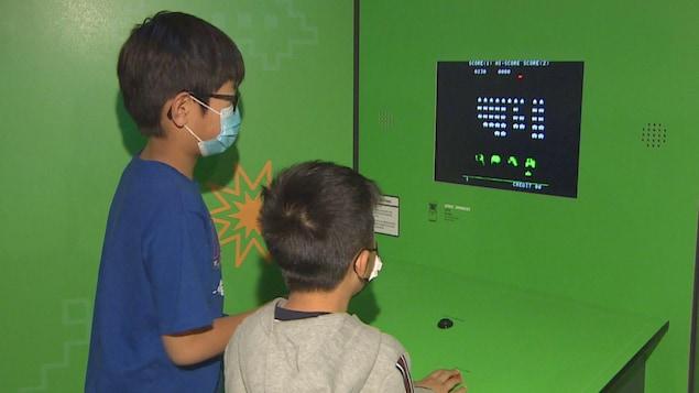 Deux enfants jouent à un jeu vidéo.