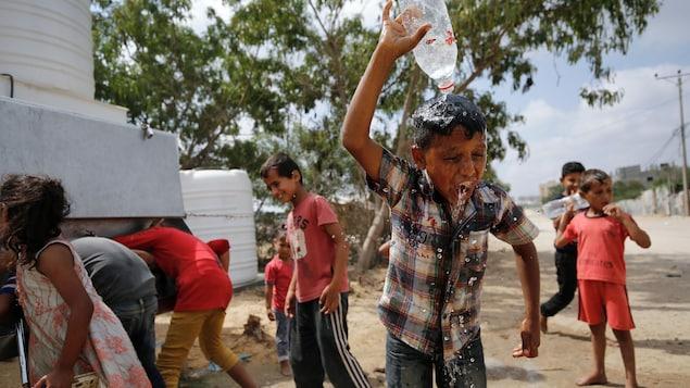 Un enfant verse de l'eau sur sa tête.