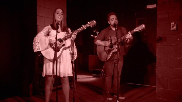 Le duo de musiciens Gen & Tonic, du Manitoba, jouant de la guitare, debout derrière des micros.