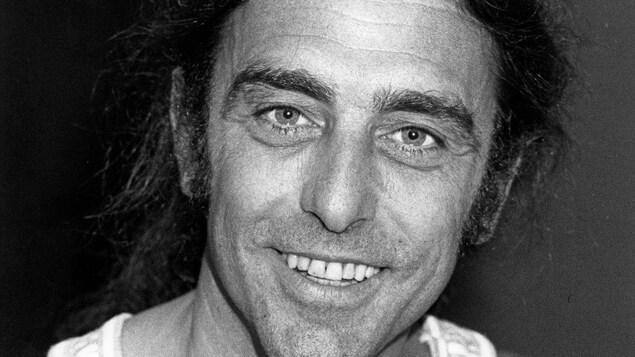 Gerry Boulet, en camisole, souriant, regarde l'objectif.