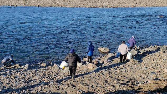 Des gens puisent de l'eau dans la rivière Sylvia Grinnell, à Iqaluit, en octobre 2021.