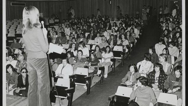 Une femme de dos tient un micro devant une foule assise dans une salle de spectacle.