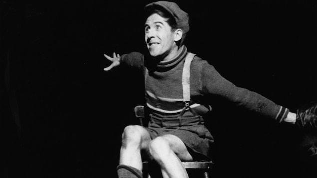 Sur une scène, Fridolin (Gratien Gélinas) est assis sur une chaise, les bras grand ouverts de chaque côté de son corps.