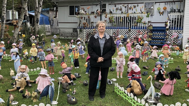 La femme est entourée de 80 poupées devant sa résidence.