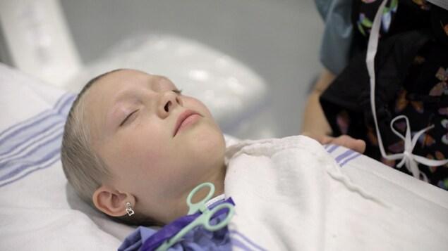 Une jeune fille aux cheveux très courts a les yeux fermés, allongée sur un lit d'hôpital.