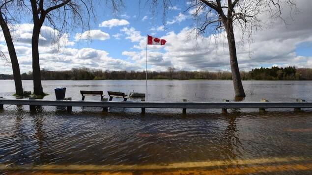 Route et berges d'une rivière engloutie en raison d'inondations.