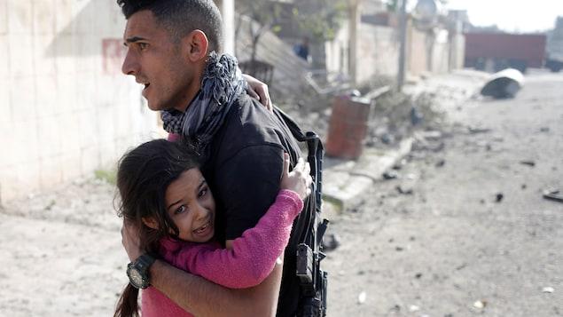 Un soldat des forces spéciales irakiennes vient en aide à une jeune civile en pleurs.