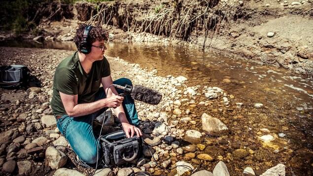Isaël Huard assis au bord d'un cours d'eau dont il capte le bruit.