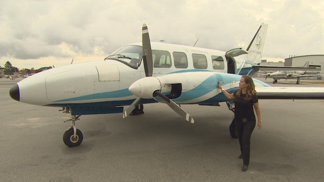 Une femme debout à côté d'un avion.