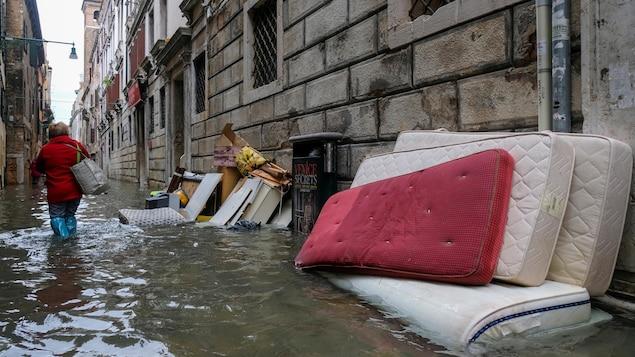 Une femme marche avec de l'eau pratiquement jusqu'aux genoux dans une rue inondée de Venise.