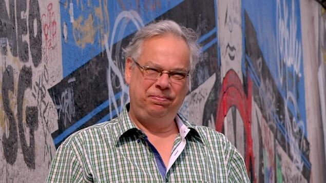 Portrait en couleur, en extérieur, de l'auteur Jacques Lemaire, devant un mur couvert de graffitis