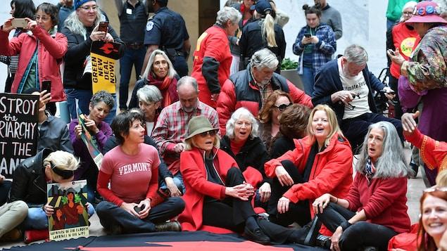 Les personnes sont assises sur le sol.
