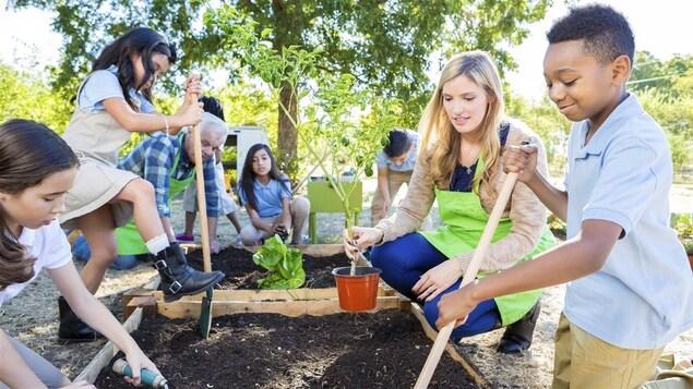 Des enfants jardinent avec deux adultes.