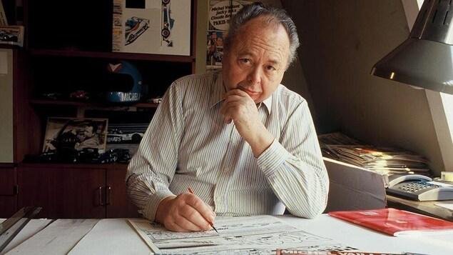 Un homme esquisse des croquis de bande dessinée assis à une table de travail.