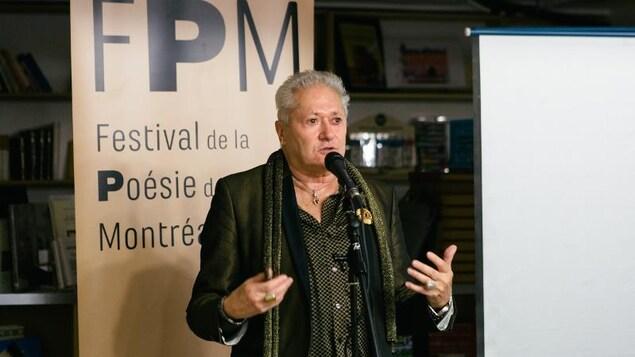 Le poète se tient debout devant un micro et parle.