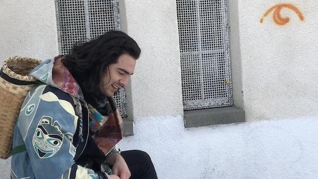 Un homme sourit en regardant au sol.