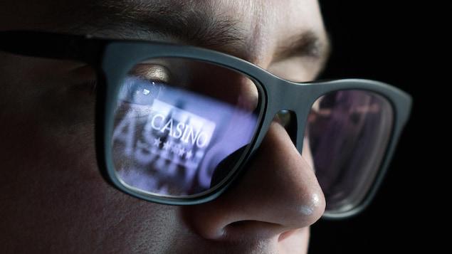 Une personne porte des lunettes fumées sur lesquelles ont peut lire le mot casino.