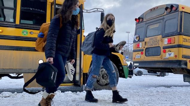 Des étudiantes débarquent de l'autobus, masqué dans une école de Québec.