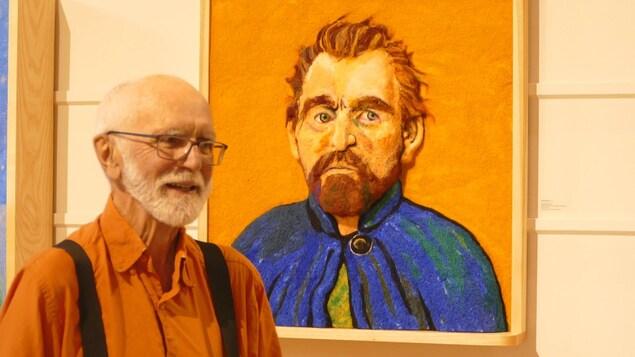 Un homme pose devant un portrait aux tonalités orange et bleue.