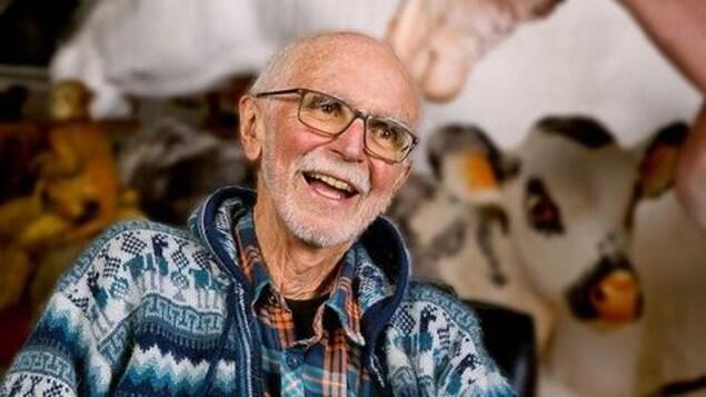 Joe Fafard assi sur une chaise, entouré par ses oeuvres, sourit à la caméra.