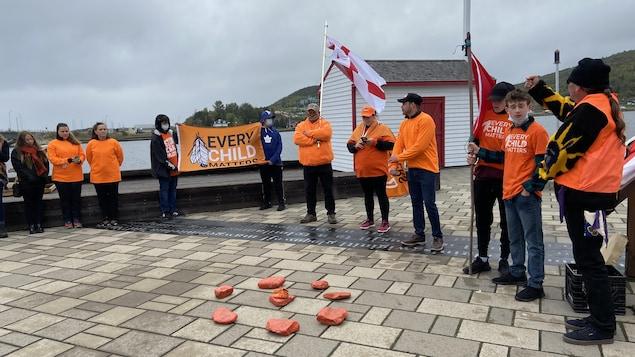 Quelques personnes entourent les sept pierres orange et une paire de souliers orange, posées sur le sol.