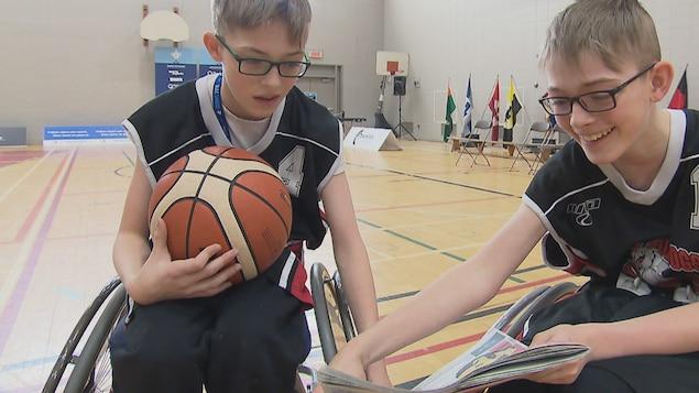 Les jumeaux Alexandre Duval et Philippe Duval regardent un article de journal sur un terrain de basketball